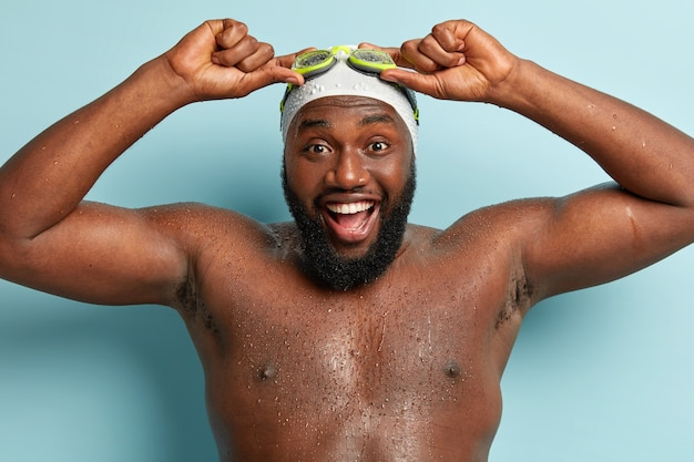 Nahaufnahme schuss des bärtigen glücklichen mannes posiert nackt, hat positive eindrücke nach dem tauchunterricht, hält hände auf brille, hat muskulösen körper und dunkle haut, steht drinnen. schwimmen, hobby, ruhekonzept
