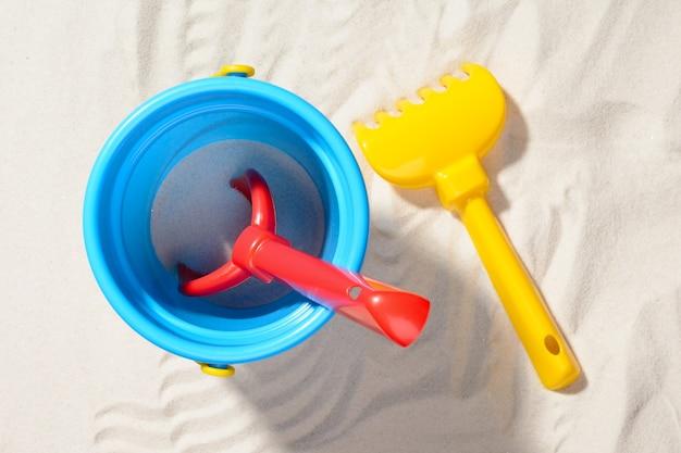 Nahaufnahme schuss des blauen eimers mit schaufel und rechen auf sand