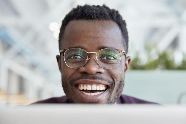 Nahaufnahme schuss des glücklichen dunkelhäutigen mannes mit breitem lächeln, weißen zähnen, trägt transparente brille für gute sicht