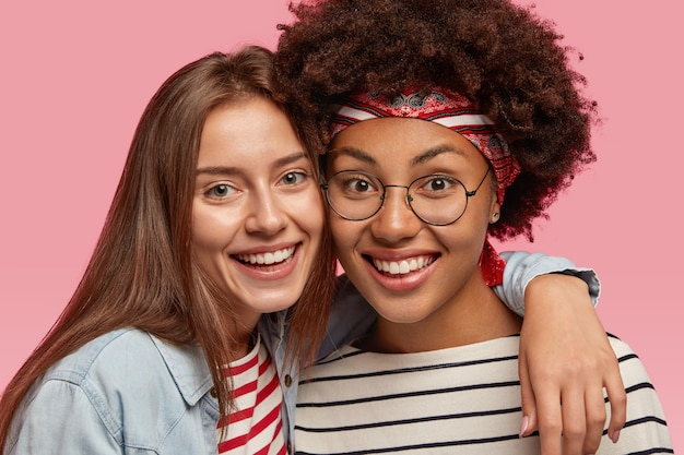 Nahaufnahme schuss des lächelns verschiedene beste freundinnen warm umarmen, glücklich aussehen, breites lächeln haben, weiße zähne zeigen