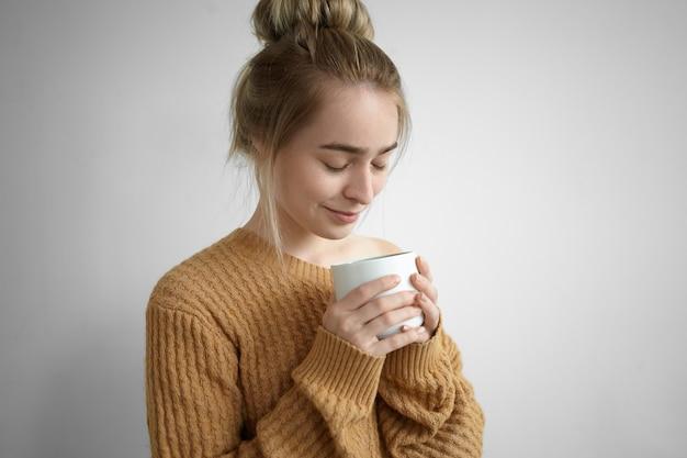 Nahaufnahme schuss des niedlichen hübschen mädchens im kuscheligen strickpullover, der süßen warmen kakao von der großen tasse genießt, augen schließt und gutes aroma des heißen getränks einatmet. getränk, ruhe, freizeit und entspannung