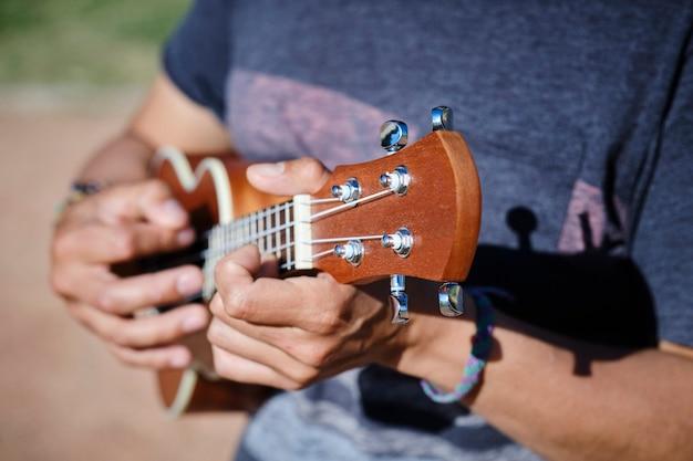 Nahaufnahme schuss einer männlichen hand, die die ukulele spielt