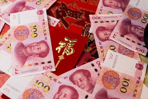 Nahaufnahme schuss von 100 chinesischen yuan (cny) banknoten und chinesischen traditionellen roten umschlag