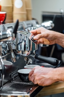Nahaufnahme schuss von barista, der filterhalter hält, während kaffeemaschine frischen espresso in glas braut