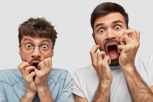 Nahaufnahme schuss von emotionalen betäubten männern starren mit abgehörten augen voller angst