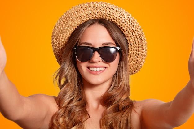 Nahaufnahme schuss von gut aussehender frau mit freundlichem lächeln, trägt trendige sonnenbrille und strohhut, macht selfie-porträt auf nicht erkennbarem gerät, macht fotos für soziale netzwerke, isoliert auf orange