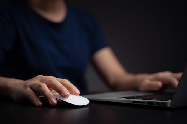 Nahaufnahme schuss von händen und maus, die mit laptop arbeiten.