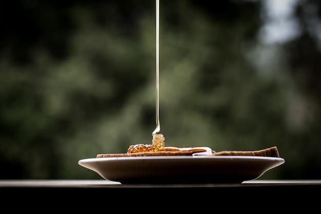 Nahaufnahme schuss von honig, der auf die brotscheiben auf einem teller gießt