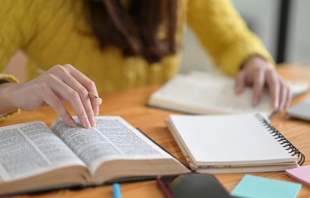 Nahaufnahme schuss von jungen frauen, die gelbe kleidung tragen, lesen bücher, um sich auf college-aufnahmeprüfungen vorzubereiten.