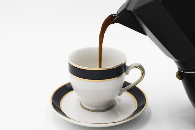 Nahaufnahme schuss von kaffee, der in die tasse von einem kessel gießt, der auf einer weißen oberfläche isoliert wird