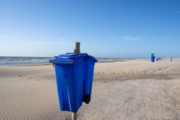 Nahaufnahme schuss von müllcontainern im strand bei sonnenuntergang