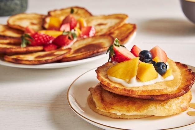 Nahaufnahme schuss von pfannkuchen mit früchten auf der oberseite beim frühstück