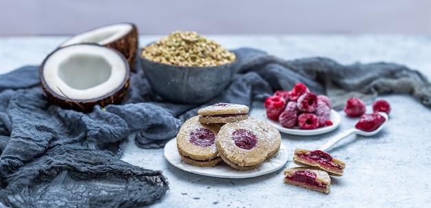 Nahaufnahme schuss von rohen veganen keksen mit kokosnuss und himbeeren
