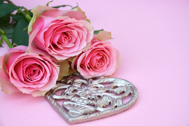 Nahaufnahme schuss von rosa rosen mit einer metallischen herzform auf einer rosa oberfläche