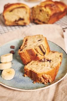 Nahaufnahme schuss von scheiben des köstlichen bananenbrotes mit schokoladenstücken und walnuss auf einem teller