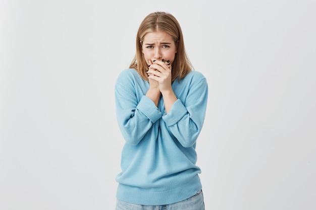 Nahaufnahme schuss von verärgertem teenager-mädchen, das blauen pullover und jeans fast weint, ihr gesicht versteckt, absolut schockiert von den schlechten nachrichten.