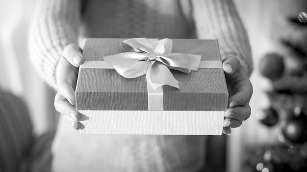 Nahaufnahme schwarz-weiß-bild der weiblichen hand, die eine schöne schachtel mit geschenk mit seidenschleifenband hält