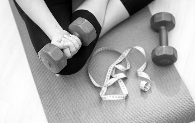 Nahaufnahme schwarz-weiß-foto der jungen frau, die auf fitnessmatte sitzt und hanteln hebt