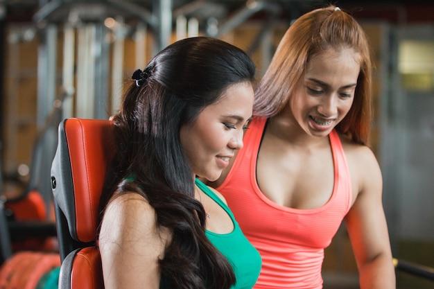 Nahaufnahme sehen attraktives mädchen, das ihre schenkel im fitnessstudio ausübt