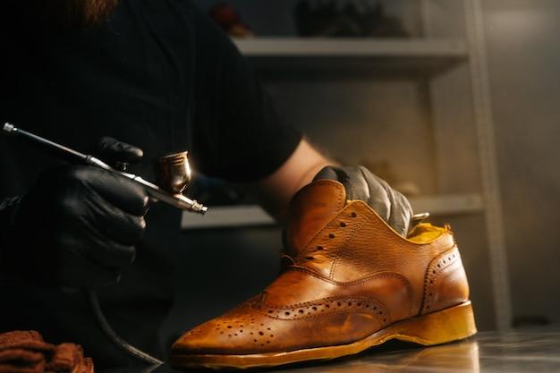 Nahaufnahme seitenansicht eines nicht erkennbaren schusters mit schwarzen handschuhen, die farbe aus hellbraunem leder sprühen...