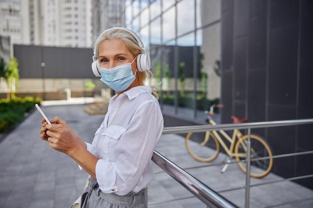 Nahaufnahme seitenansicht porträt einer fröhlichen, fröhlichen frau in schutzmaske mit kopfhörern, die vor einem modernen gebäude in der stadt stehen