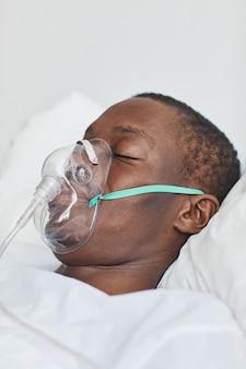 Nahaufnahme seitenansicht porträt eines afroamerikanischen mannes im krankenhausbett mit sauerstoffmaske