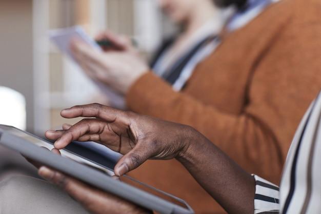 Nahaufnahme seitenansicht von leuten, die auf einer geschäftskonferenz in reihe sitzen, konzentrieren sie sich auf afroamerikanische weibliche hände, die ein digitales tablet im vordergrund halten, kopienraum