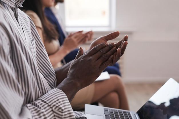 Nahaufnahme seitenansicht von leuten, die auf einer geschäftskonferenz in reihe sitzen, konzentrieren sie sich auf afroamerikanische weibliche hände, die im vordergrund applaudieren, platz kopieren