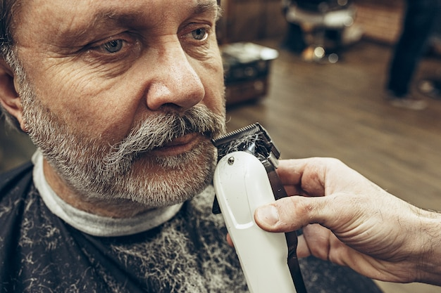 Nahaufnahme-seitenansichtporträt des hübschen älteren bärtigen kaukasischen mannes, der bartpflege im modernen friseursalon erhält.