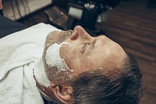 Nahaufnahme seitlicher draufsicht hübscher älterer bärtiger kaukasischer mann, der bartpflege im modernen friseursalon erhält.