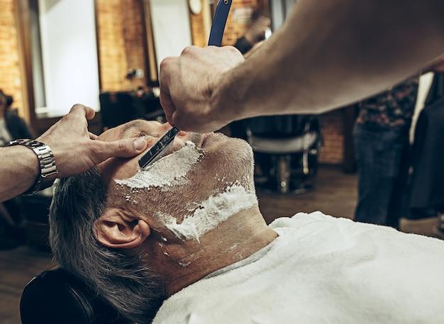 Nahaufnahme seitlicher draufsicht schöner älterer bärtiger kaukasischer mann, der bartpflege im modernen friseursalon erhält.