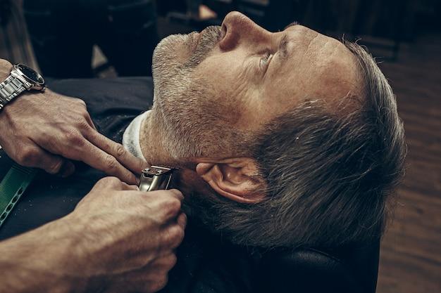 Nahaufnahme seitlicher rückansicht schöner älterer bärtiger kaukasischer mann, der bartpflege im modernen friseursalon erhält.