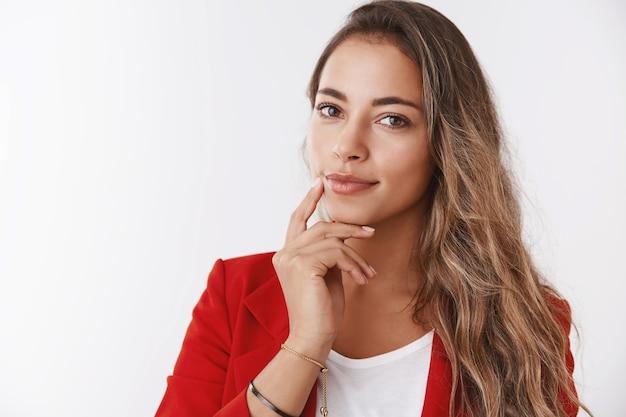 Nahaufnahme selbstbewusste erfolgreiche reiche geschäftsfrau mit roter jacke, die den kiefer berührt, lächelnd, selbstbewusst aussehende kamera intelligent intelligent, weiß, wie das geschäft aufrechterhalten wird, kunden anzuziehen