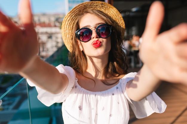Nahaufnahme selfie-porträt des lustigen mädchens mit dem langen haar, das auf sonnenlicht auf terrasse steht. sie trägt ein weißes kleid, einen hut, einen roten lippenstift und eine sonnenbrille. sie schickt einen kuss in die kamera.