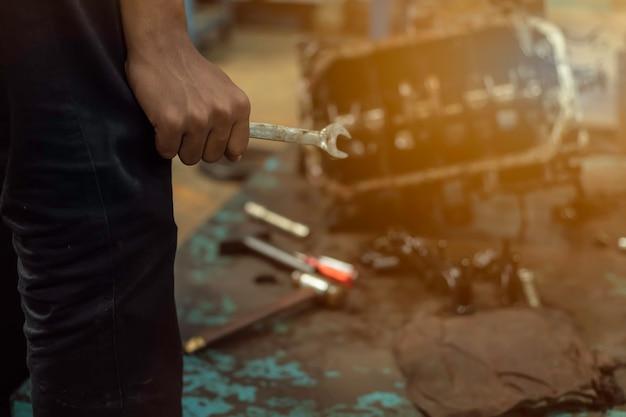 Nahaufnahme, serviceauto ist menschen reparieren ein auto verwenden sie einen schraubenschlüssel und einen schraubendreher, um zu arbeiten. motorreparaturtechniker halten den schlüssel, um das auto zu reparieren.