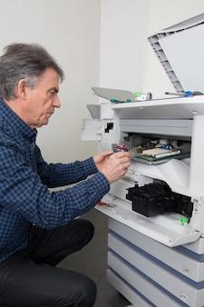 Nahaufnahme shotmale techniker, der digitales fotokopiergerät repariert
