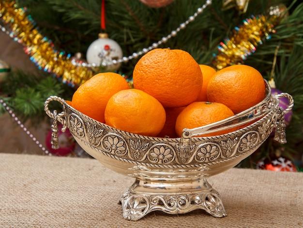 Nahaufnahme silberne vase mit orangen auf sackleinen und weihnachtsbaum mit spielzeugbällen und girlanden im hintergrund.