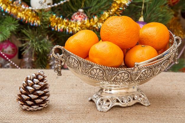 Nahaufnahme silberne vase mit orangen und einem kegel auf sackleinen und weihnachtsbaum mit spielzeugbällen und girlanden im hintergrund.