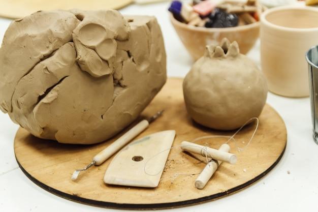 Nahaufnahme skulptur werkzeuge auf tisch gesetzt, tonstapel, einige profile.