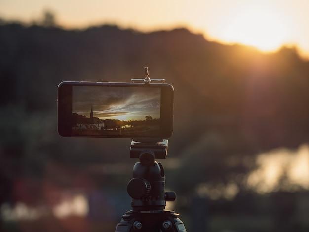 Nahaufnahme smartphone machen ein landschaftsfoto und video zeitraffer auf standstativ im sonnenuntergang.