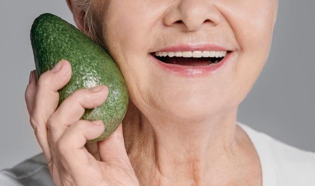 Nahaufnahme-smiley-frau, die avocado hält