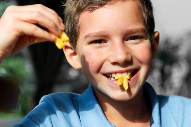 Nahaufnahme smiley junge, der pommes frites isst