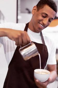 Nahaufnahme smiley-mann, der kaffee macht