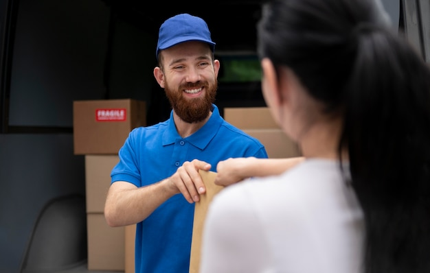 Nahaufnahme smiley-mann, der paket liefert