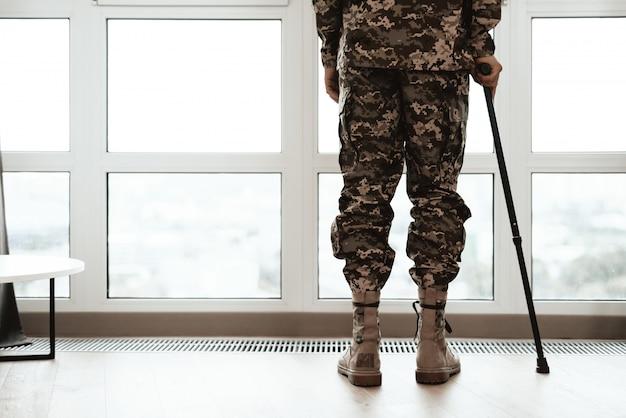 Nahaufnahme-soldat-beine, die auf krücke durch fenster sich lehnen.