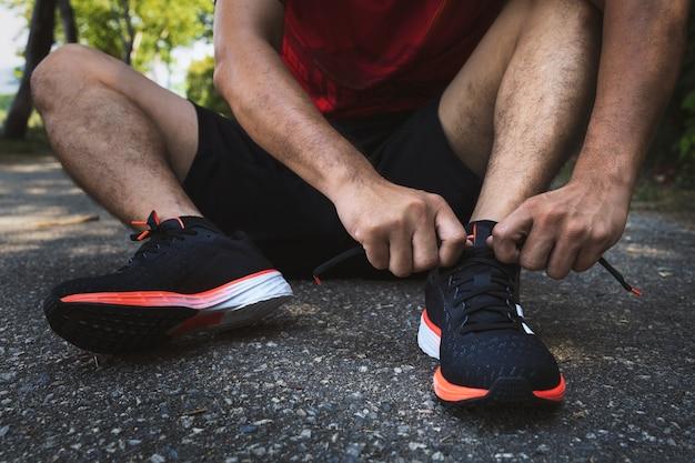 Nahaufnahme-sportler, der laufschuhe mit weichzeichner und über licht im hintergrund bindet. konzept für fitness, bewegung, training und gesunden lebensstil.
