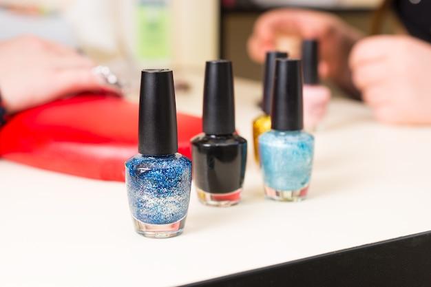 Nahaufnahme stillleben mit nagellackflaschen in verschiedenen farben auf maniküretisch im salon - vielzahl von nagellack in blau- und schwarztönen im spa