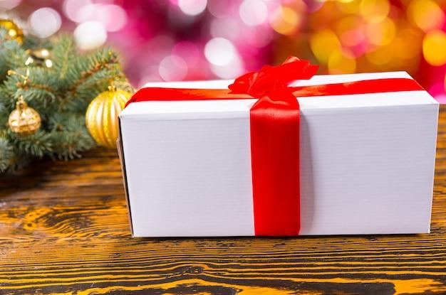 Nahaufnahme stillleben mit weißem geschenk verpackt mit leuchtend roter schleife und sitzen auf dem tisch mit holzmaserung neben festlicher weihnachtsdekoration aus kiefernzweigen