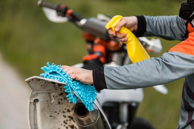 Nahaufnahme stilvoller mann, der motorrad reinigt