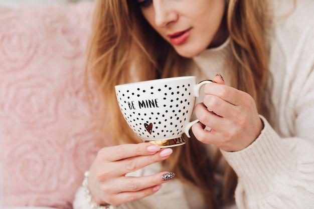 Nahaufnahme stock foto einer jungen blonden frau mit einer süßen kaffeetasse mit goldenem design und text gehören mir. morgenkaffee in einer schönen kaffeetasse.
